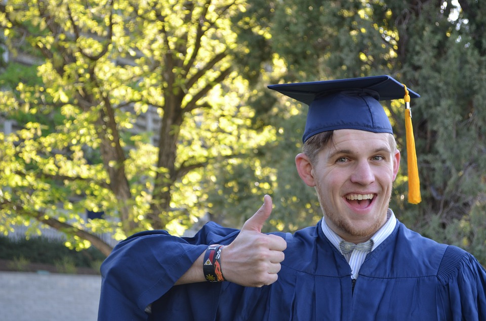 Graduate wearing a cap and gown, doing a thumbs up