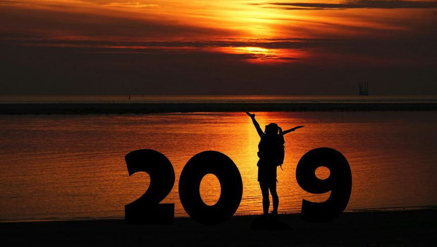 '2019' spelt out in front of a sunset on a beach, where the '1' is a person with their arms splayed.