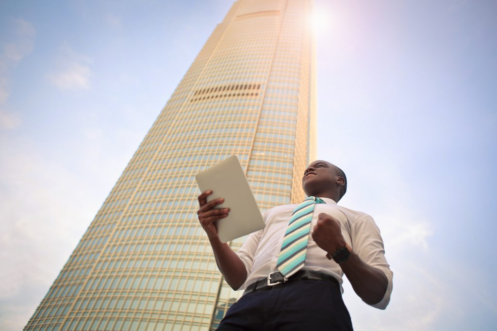 A man standing in front of a skyscraper celebrates